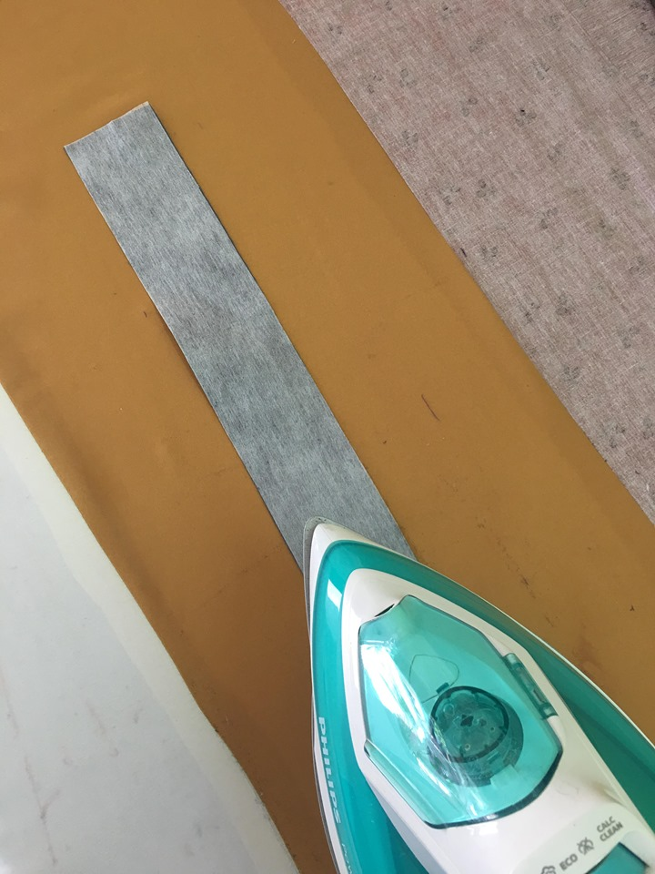 จากนั้นนำผ้ากาวที่เหลืออีก1ชิ้น ไปรีดติดด้านผิด ของผ้าชิ้นสาบที่ตัดเท่าแพทเทริ์นเมื่อสักครู่