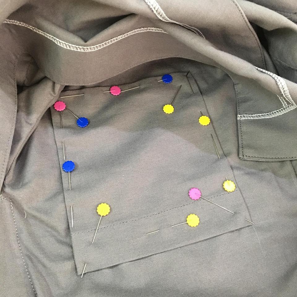 นำชิ้นกระเป๋าไปวางบนตำแหน่งที่มาร์คไว้ ใช้เข็มกลัดยึดไว้ แล้วเย็บทั้งสามด้านติดกับตัวชุดได้เลยค่ะ