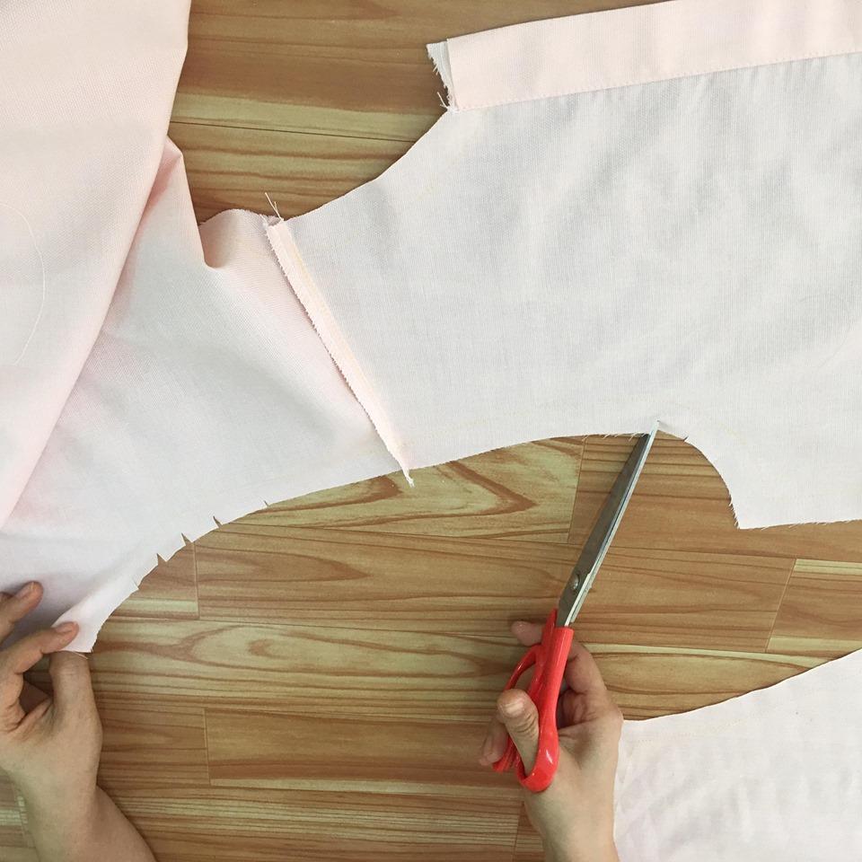 ขลิบตะเข็บบริเวณแนวโค้งของผ้าส่วนที่จะต่อกับแขนเสื้อทั้งสองเล็กน้อย