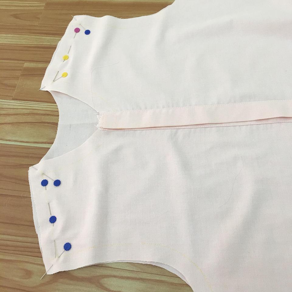 นำผ้าชิ้นตัวเสื้อชิ้นหน้าและชิ้นหลังมาประกบกัน ด้านถูกประกบด้านุูถูก ไหล่ซ้ายตรงไหล่ซ้าย ไหล่ขวาตรงไหล่ขวา ใช้เข็มหมุดกลัดเส้นเย็บบริเวณไหล่ซ้ายกับไหล่ขวา ของตัวเสื้อชิ้นหน้าและหลังให้ตรงกัน จากนั้นเย็บตามเส้นเย็บบริเวณไหล่ซ้านและขวา จากนั้นตัดตะเข็บให้เหลือ 1 cm แล้วนำไปโพ้งตะเข็บรวมทั้งไหล่ซ้ายและไหล่ขวา แล้วนำมารีดล้มตะเข็บไปทางผ้าชิ้นหลัง