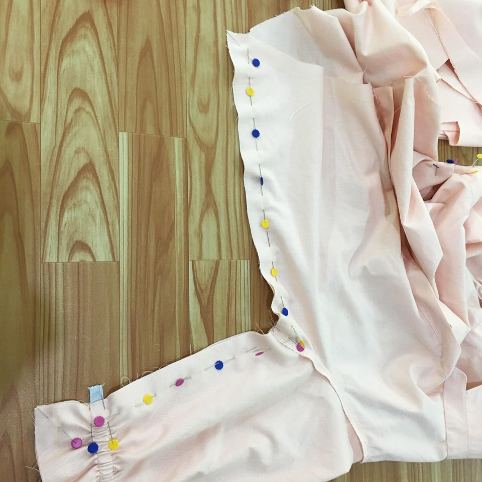 ประกบตัวเสื้อชิ้นหน้าแล้วชิ้นหลัง ให้ด้านถูกประกบด้านถูก ใช้เข็มหมุดกลัดแนวเส้นเย็บ ส่วนแขนจนถึงข้างตัวเสื้อไว้ แล้วนำไปเย็บตามเส้นเย็บ