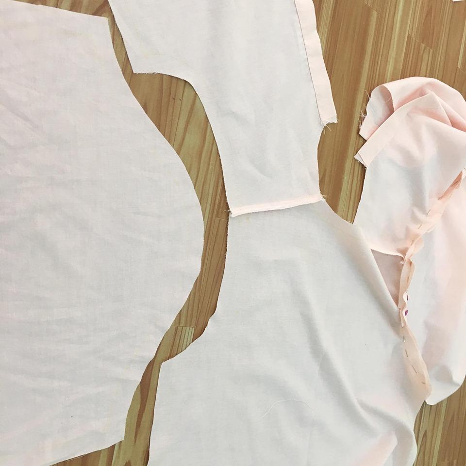 นำผ้าชิ้นแขนเสื้อมาประกบกับผ้าชิ้นตัวเสื้อ ถูกประกบถูก กลัดเข็มหมุดยึดเส้นแนวเย็บให้ตรงกัน